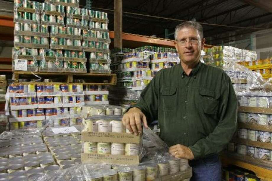 Tom Urich, operations director at Second Mile Mission Center in Stafford, stands beside pallets of food that will be distributed as part of traditional Thanksgiving dinners for 1,000 families at the Stafford Centre on Tuesday. Photo: Suzanne Rehak, For The Chronicle