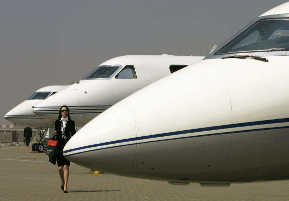 A visitor walks past Gulfstream business jets at the Asia Business Aviation Conference & Exhibition in Hong Kong. Some in Congress pounced on what they view as the hypocrisy of auto executives flying on corporate jets to Washington to ask for public help. But defenders say that what some call a lavish perk is in reality a necessary security requirement and productivity booster. Photo: Associated Press File