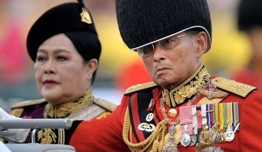 Thai King Bhumibol Adulyadej and Queen Sirikit review the honor guard Tuesday at the Royal Plaza. Photo: PORNCHAI KITTIWONGSAKUL, AFP/GETTY IMAGES