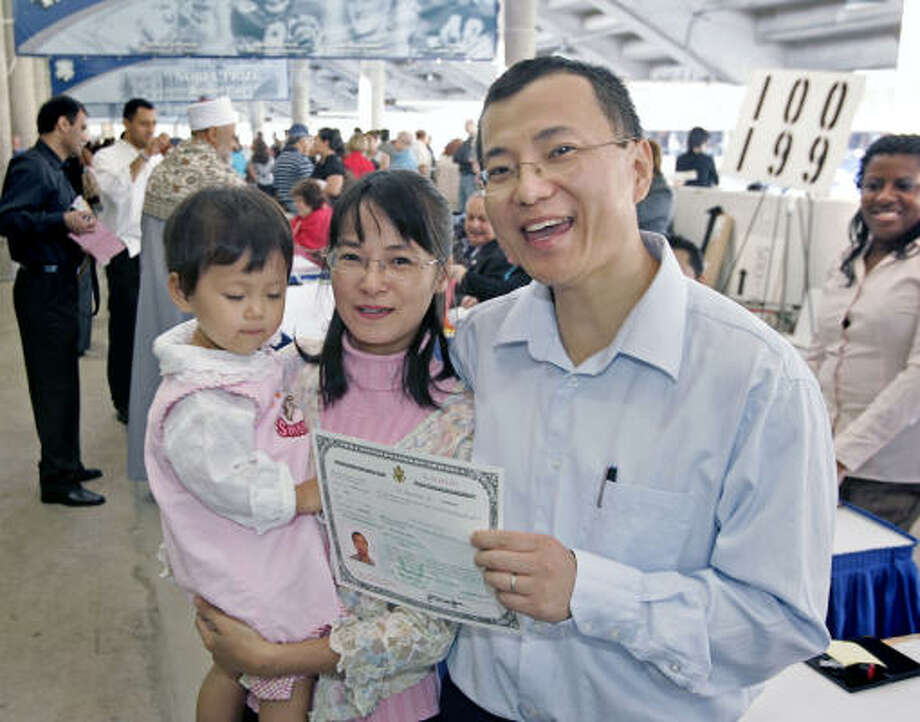 Feng Li, originally of mainland China, is sworn in while accompanied by his wife Yan F. Huang and daughter Cynthia. Photo: Craig Hartley, For The Chronicle