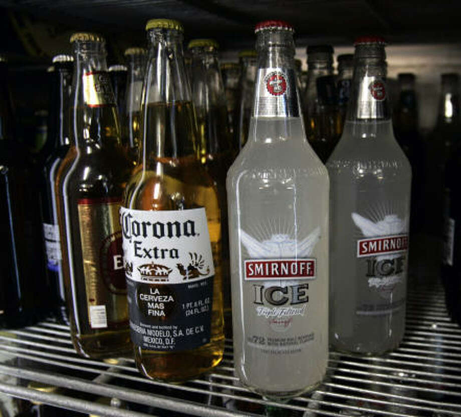 Bottles of Smirnoff Ice are seen on a cooler shelf at a store in Albany, N.Y., on Monday. New York Gov. Eliot Spitzer wants to redefine flavored alcohol drinks as liquor instead of beer, which would increase tax revenue. Photo: Mike Groll, Associated Press