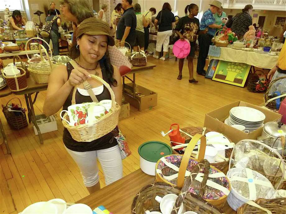 Mariela Gonzalez of Fairfield considers a purchase in the housewares area of the Operation Hope tag sale Saturday at First Church Congregational. Photo: Mike Lauterborn / Fairfield Citizen contributed