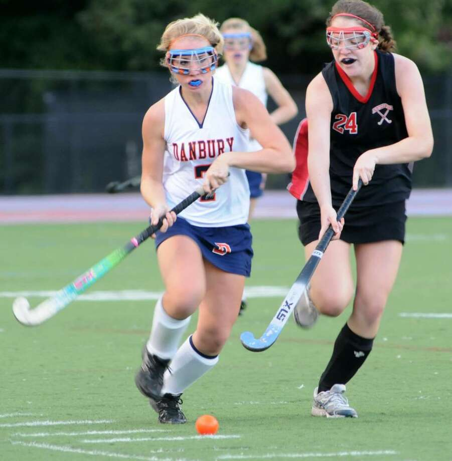 Alison Scott, #7, of Danbury High School, Danbury, CT drives the ball up field as Fairfield's Sarah Maisel, #24, of Warde High School, Fairfield, CT plays defense on Thursday, Oct. 1, 2009 at the girls field hockey game played at Danbury High School. Photo: Jay Weir / The News-Times