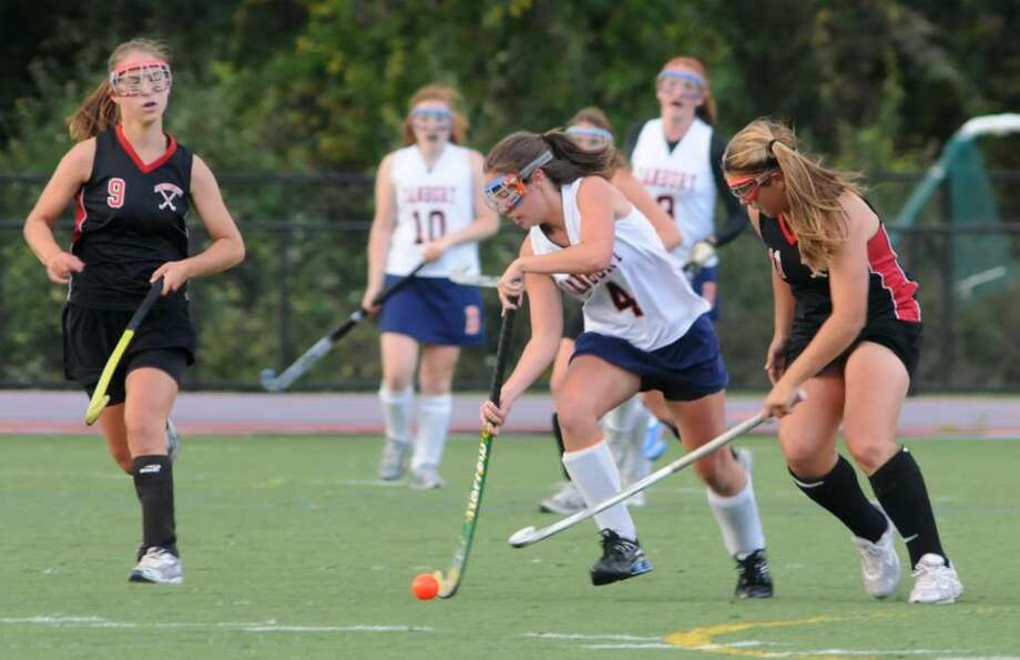 Alli George, #4, of Danbury High School, Danbury, CT controls the ball as Molly Brachfeld,#9, left and Stacey Dileo, #11, right, of Warde High School in Fairfield, CT try to make the steal on Thursday, Oct. 1, 2009 at the girls field hockey game at Danbury High School. Photo: Jay Weir / The News-Times