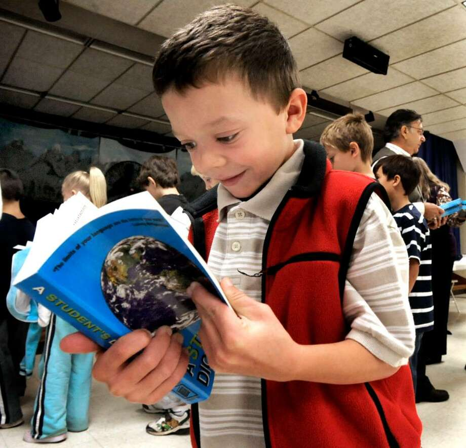 Patrick Williston, 3rd grade in Redding Elementry School, looking at the dictionary he was given by The Redding Grange on Friday, Oct.2,2009. Photo: Michael Duffy / The News-Times