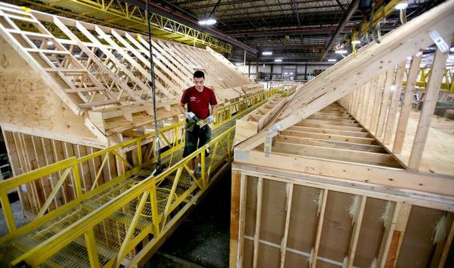 Byron Rodas works on the roof line of a modular home in a Wingdale, N.Y., factory. Home prices dropped a record 15.4 percent in the second quarter. Photo: CRAIG RUTTLE, ASSOCIATED PRESS