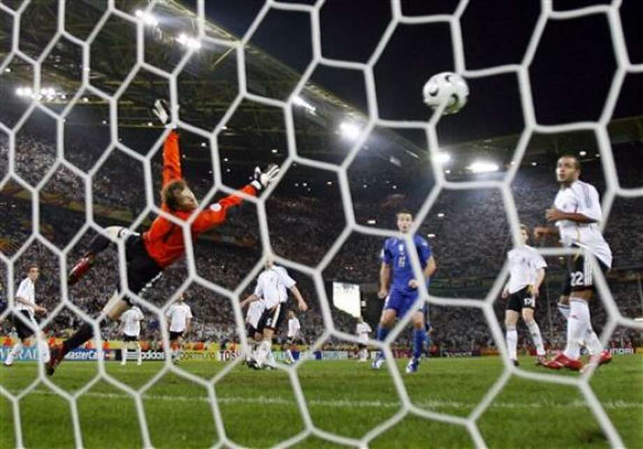 Germany's goalkeeper Jens Lehmann, left, dives in attempt to stop Italy's first goal by Fabio Grosso, not seen, in the extra time of  a World Cup semifinal Tuesday.  Italy won 2-0. Photo: LUCA BRUNO, ASSOCIATED PRESS