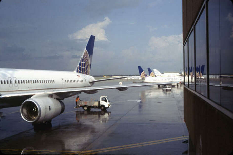 A worker services a Continental Airlines Boeing 757 that had just pulled into a gate at Bush Intercontinental Airport. Speculation about a possible merger involving the airline has stirred concern in Houston's business community. Photo: Bill Montgomery, Chronicle