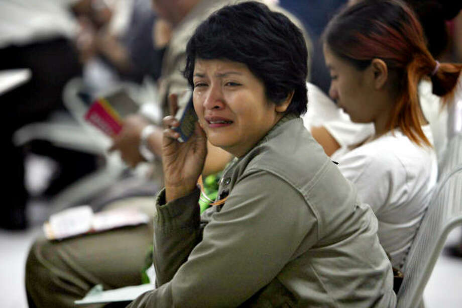 A relative of a passenger on the missing plane waits at the airport Tuesday. False reports that a dozen people may have survived brought anguish and hope to waiting relatives. Photo: ASTRIT WISKEY, AP