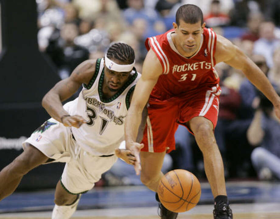 Minnesota's Ricky Davis and Rockets forward Shane Battier race for a loose ball in first quarter. Photo: Jim Mone, AP