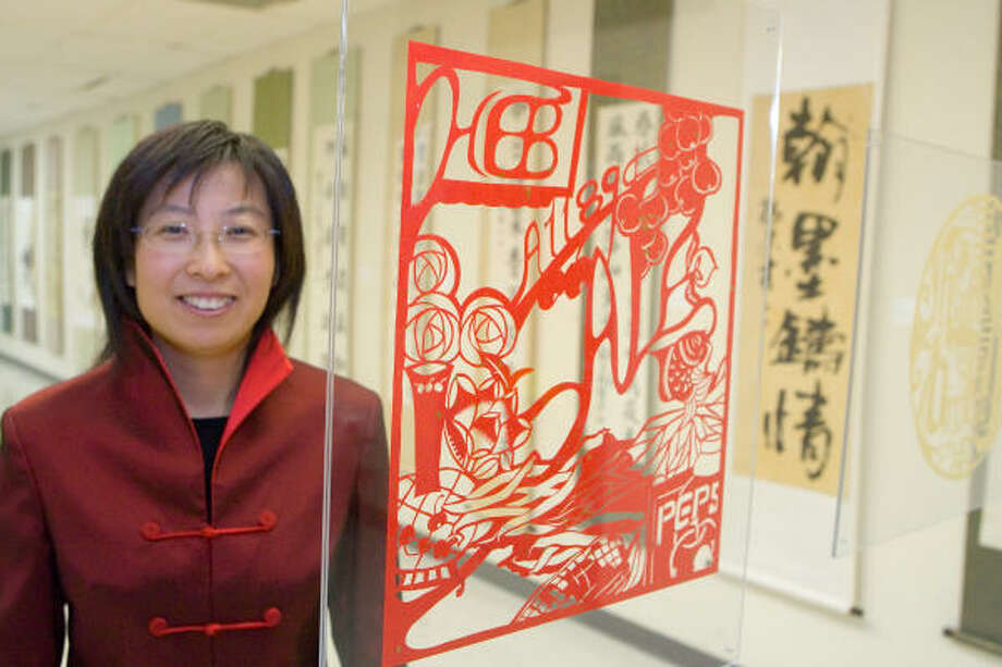 Artist Li Qiao stands next to her piece, HEB Flyer, which was exhibited with other artwork at the Chinese Civic Center, 5905 Sovereign Drive. Photo: R. Clayton McKee, For The Chronicle