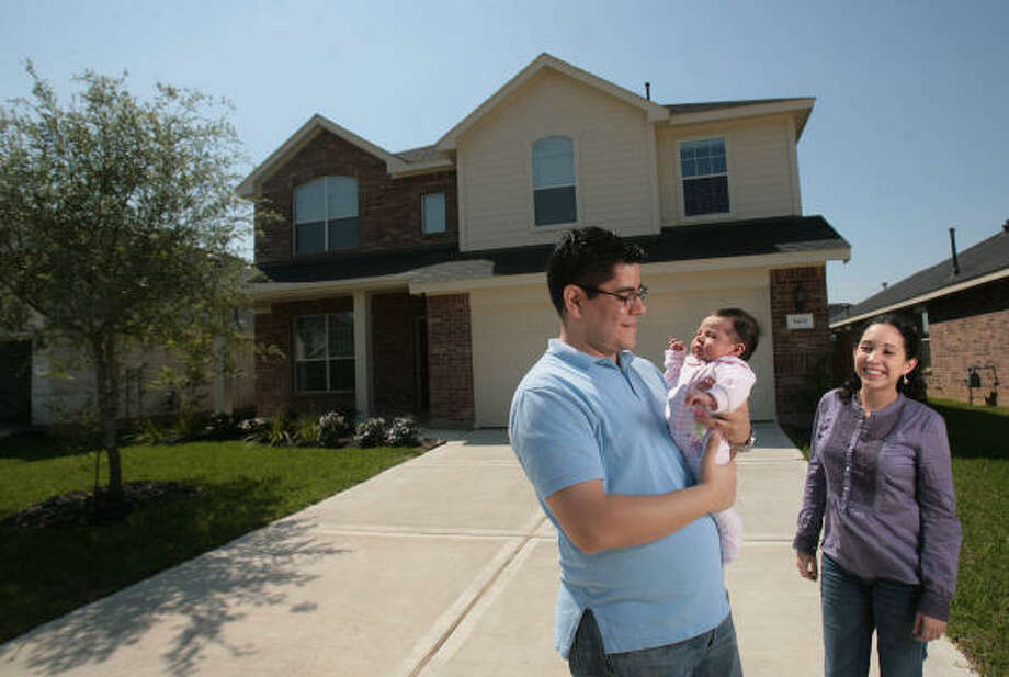 Nicolas Castro and his wife, Jannet Duran, hold daughter, Sofia, in front of their new home in the Gleannloch Farms subdivision in Spring. Photo: Mayra Beltran, Chronicle