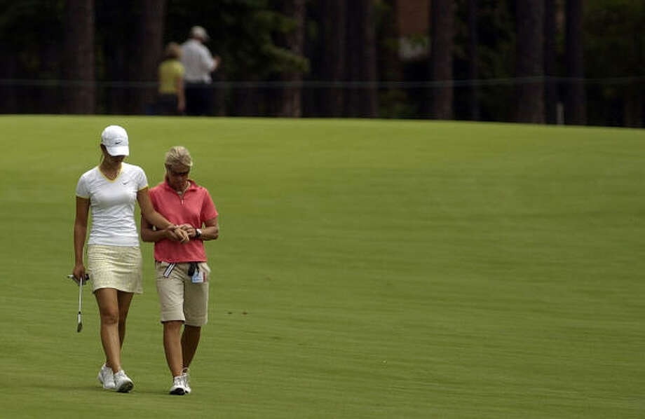 Michelle Wie gets her wrist examined by her physical therapist Leanne Quinn as they make their way down the 18th fairway at Pine Needles. Photo: Stephanie Bruce, AP