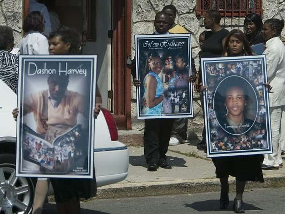 Photographs of the victims, Dashon Harvey, Iofemi Hightower and Terrance Aeriel, are held outside their funeral Saturday. The three, plus a fourth who survived, were shot in the head on a schoolyard. Photo: TIM LARSEN, ASSOCIATED PRESS
