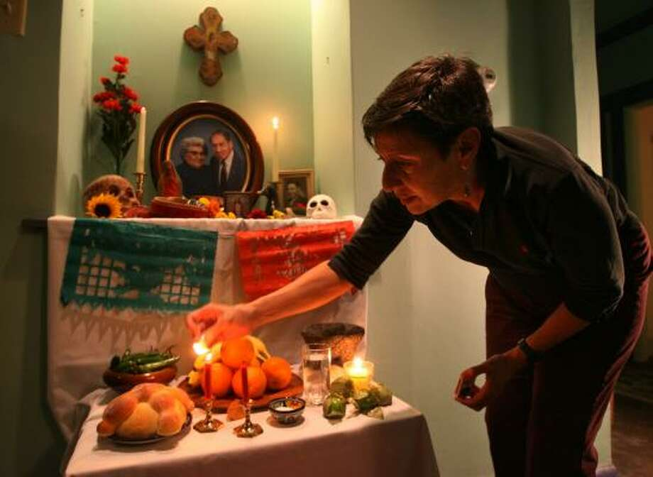 Sarah Cortez lights the candles on the altar dedicated to her father and mother for the celebration of the Day of the Dead. Photo: MAYRA BELTRÁN, CHRONICLE