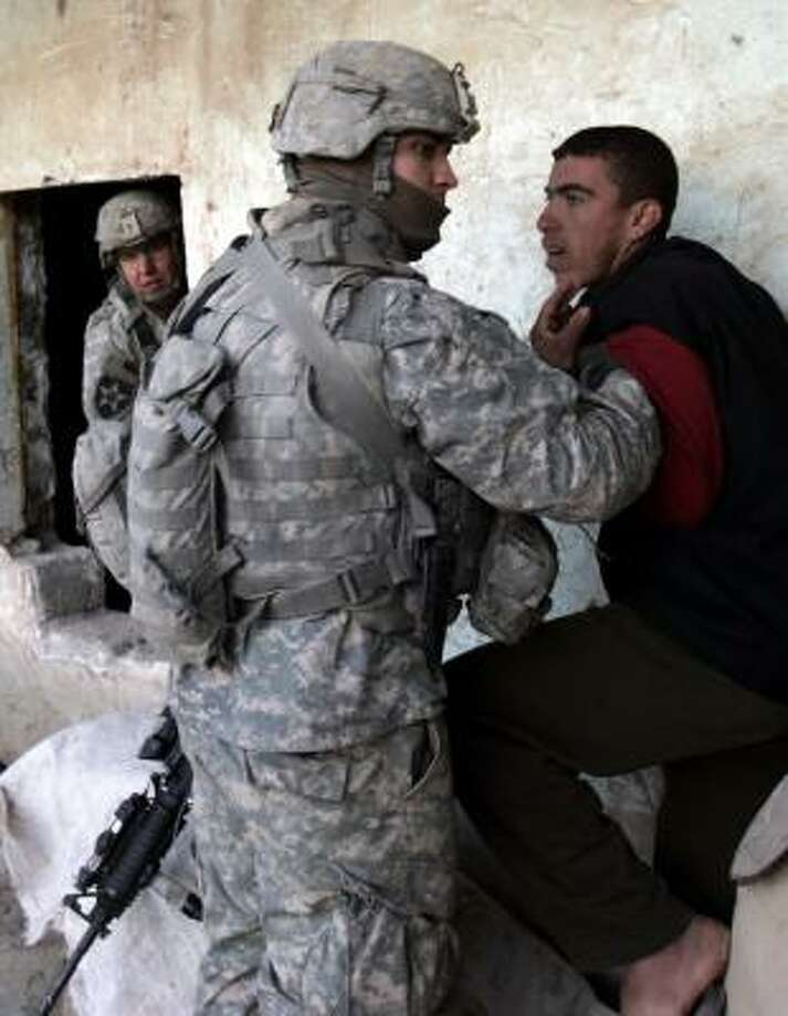 A U.S. Army soldier detains a suspect Tuesday in the town of Muqdadiyah during the initial phase of Operation Raider Harvest. Photo: KMARKO DROBNJAKOVIC, ASSOCIATED PRESS