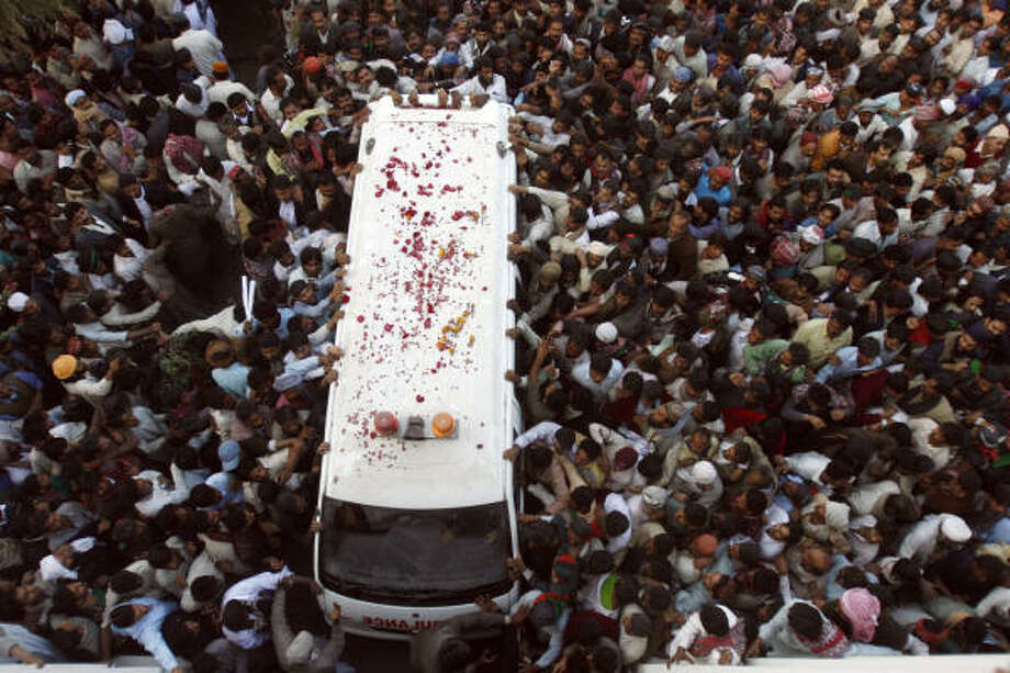 Supporters of Pakistan's former Prime Minister Benazir Bhutto surround an ambulance carrying her remains for burial at her ancestral grave in Gari Khuda Bux, Pakistan, last month. Photo: Shakil Adil, Associated Press