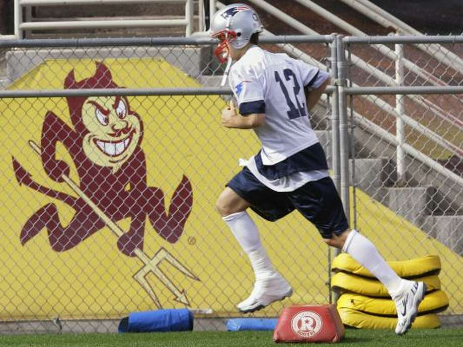 Patriots quarterback Tom Brady didn't have a devil of a time running, but he did limp on his heavily taped right ankle during Monday's practice at Arizona State. Photo: STEPHAN SAVOIA, ASSOCIATED PRESS