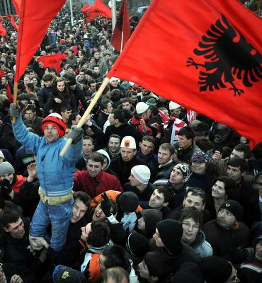 Kosovars wave Albanian flags Sunday as they celebrate independence. Photo: DIMITAR DILKOFF, AFP/GETTY IMAGES