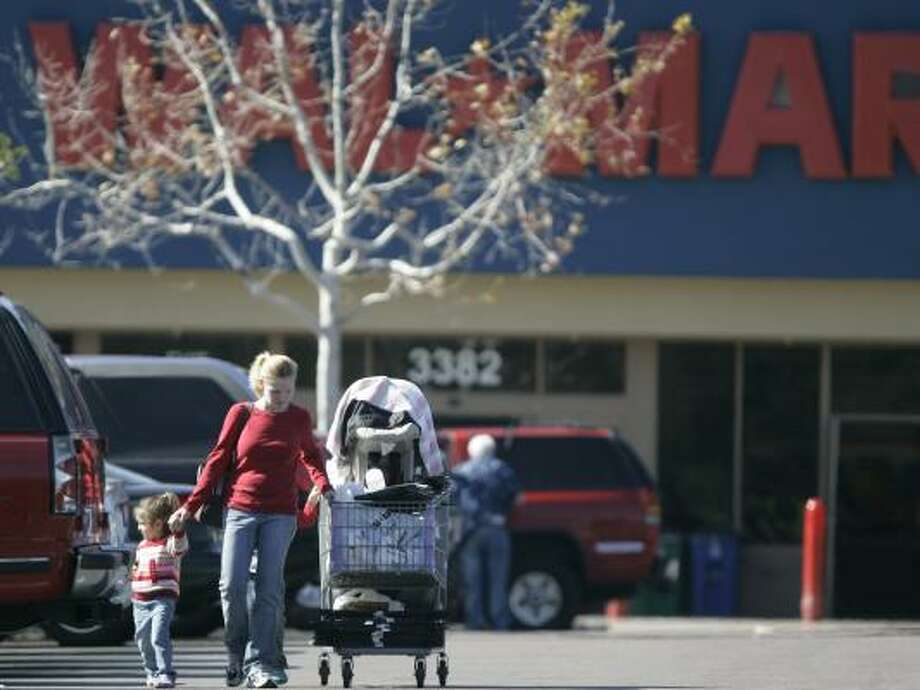 Ashley Tarbox guides her shopping cart and her three children through a Wal-Mart parking lot in San Diego on Thursday. The giant retailer reported that many shoppers are redeeming holiday gift cards for basic items like food and soap instead of iPods or DVDs. Photo: LENNY IGNELZI, ASSOCIATED PRESS
