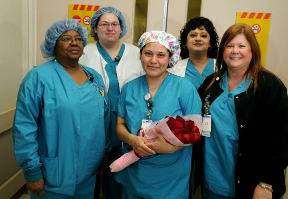 Martha Martinez, center, a surgical technician at Memorial Hermann Hospital-Northeast in Humble, was recently honored with a city proclamation by Mayor Donald McMannes for her rescue of a man from a burning vehicle on April 6. Martinez was joined by co-workers, from left, Joyce Nelms, Yvonne Jimenez, Rebecca Pradhan and Becky Neimaner. Photo: Jerry Baker, For The Chronicle