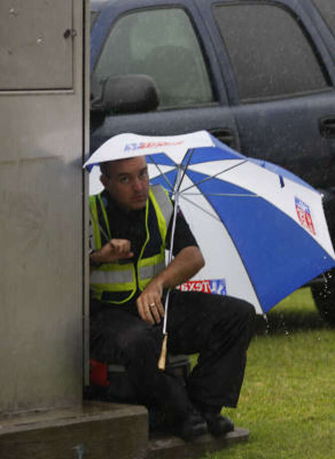 A police officer manually controlling traffic signals near Reliant Stadium huddles under an umbrella today as heavy rains pass through the area. The officer, not from Houston and working a second job, declined to give his name. Photo: Steve Ueckert, Chronicle
