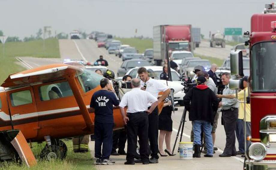 Allen Braden, of Houston, in dark jacket with his back to the camera, stands safely on a busy U.S. 75 in Tulsa, Okla., after engine failure Wednesday forced him to land on the highway. It was Braden's second time in 45 years of flying to be forced to land on a roadway. Photo: ROBERT S. CROSS, TULSA TRIBUNE