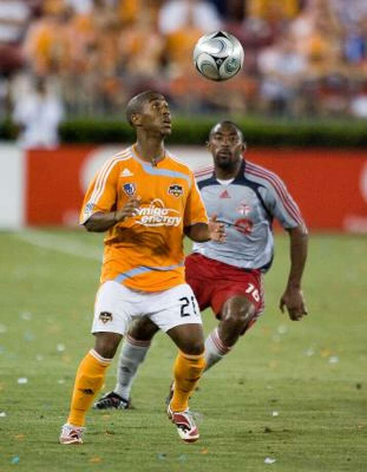 The Dynamo's Corey Ashe concentrates on the ball as he is defended by Toronto FC's  Marvell Wynne during second half. Photo: BOB LEVEY, AP