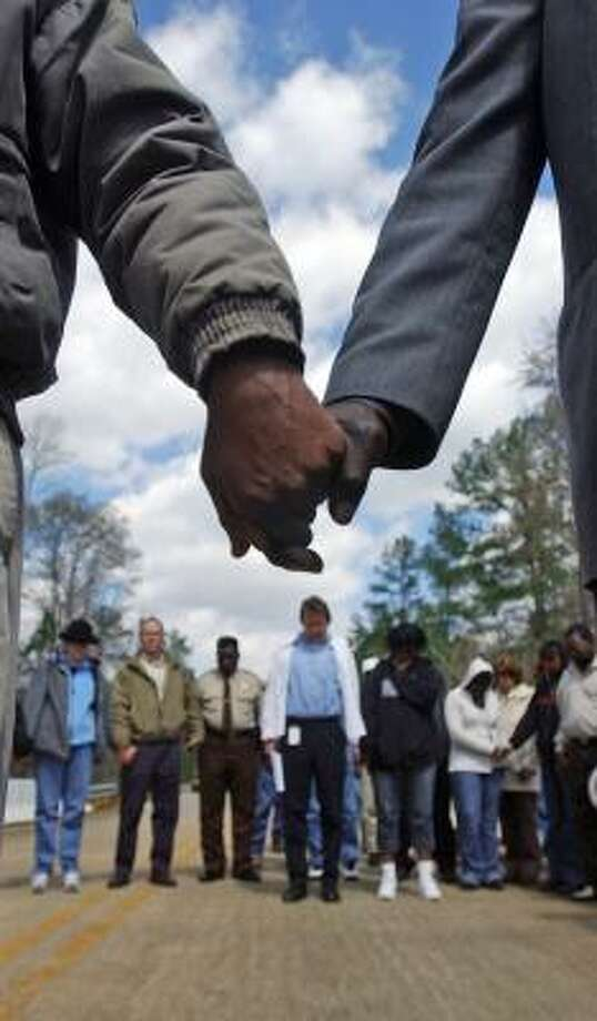 Marchers hold hands and pray for justice for the victims on Moore's Ford Bridge. Photo: R.C. RIQUE, ATHENS BANNER-HERALD