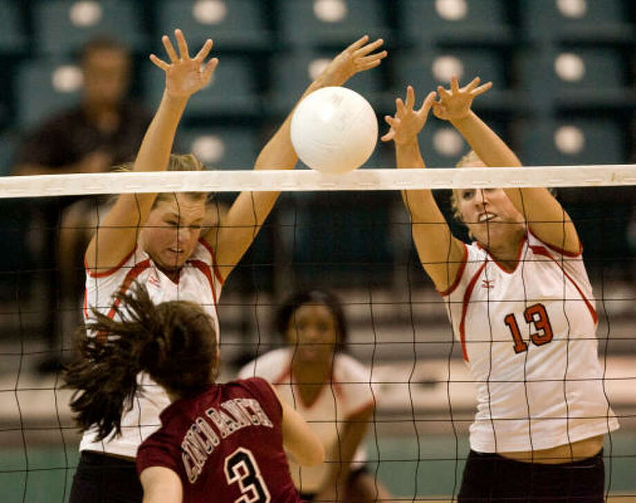 Cinco Ranch's Rachel Fairbanks has her shot stuffed by Katy's  Jessica Accord, left, and Shannon Adams during the finals of the  Katy ISD Volleyball Tournament Aug. 16. Photo: Bob Levey
