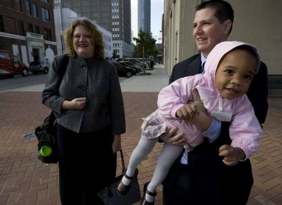 Rachel and Karrion Dashna brave colder temps as they head to the Harris County Juvenile Justice Center in downtown Houston to adopt their foster child, Claire, 2. Judges approved new parents Friday in three different courtrooms. Photo: JOHNNY HANSON, CHRONICLE