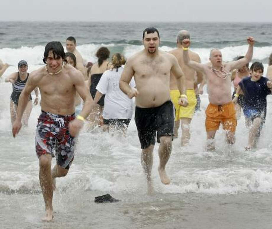 Participants in the 19th annual Lobster Dip run out of the Atlantic Ocean in Old Orchard Beach, Maine, on Jan. 1, 2007. Photo: JOEL PAGE, ASSOCIATED PRESS FILE