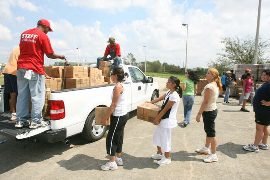 Volunteers in Houston help load a truck full of MREs for Ike's victims on Saturday. Photo: Bill Olive, For The Chronicle