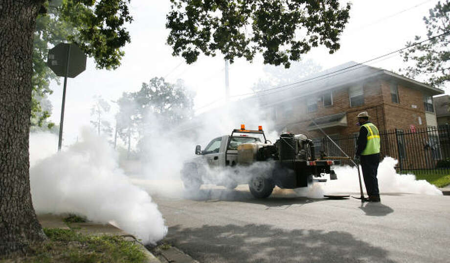 Jeremy Vela, a mosquito control inspector with Harris County Public Health and Environmental Services, observes his crew's thermal fogging operation in Houston's Museum District on Wednesday. Photo: Karen Warren, Chronicle