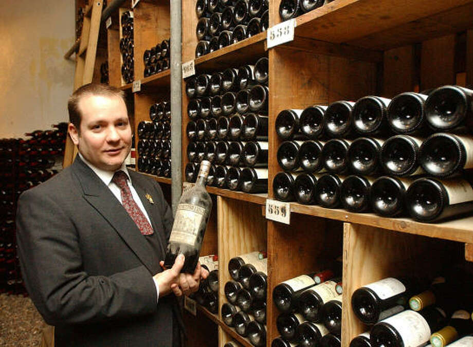 Sommelier Marco Pelletier displays a 1929 bottle of Haut-Brion in the wine cellar at Taillevent, one of Paris' most esteemed restaurants. Photo: REMY DE LA MAUVINIERE, Associated Press