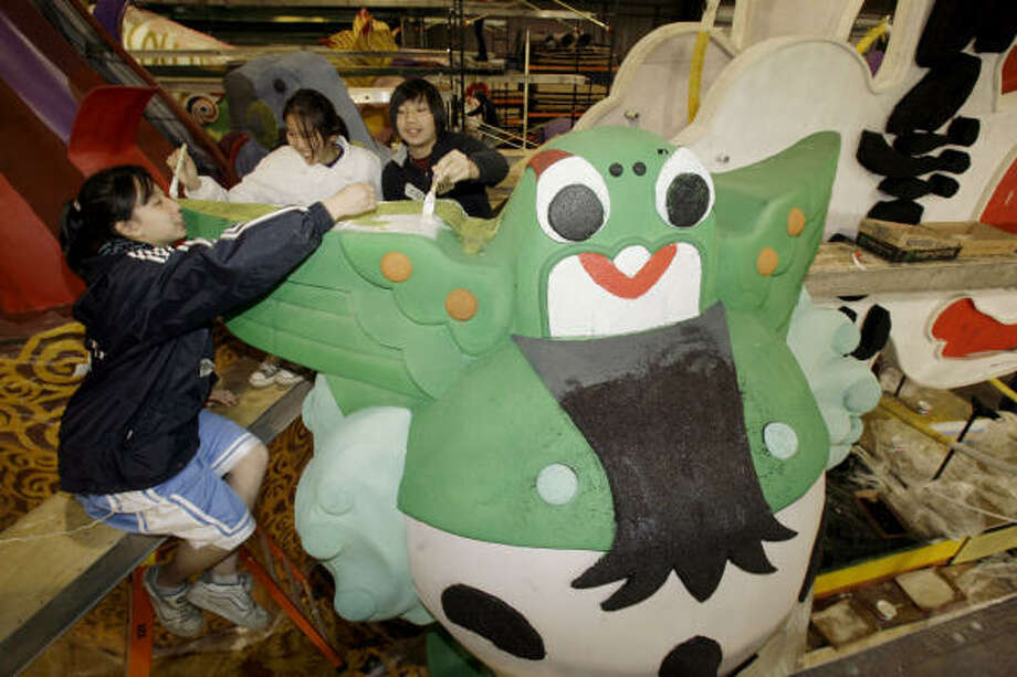 Student volunteers, from left, Jacqueline Bao, Elaine Wong and Eric Lin paint an Olympic themed float showing the five official mascots of the 2008 Beijing Olympics, during preparations Friday in Azusa, Calif., for the Rose Parade on New Year's Day. Human rights activists plan to protest this float honoring the 2008 Beijing Olympic Games. Photo: Nick Ut, AP