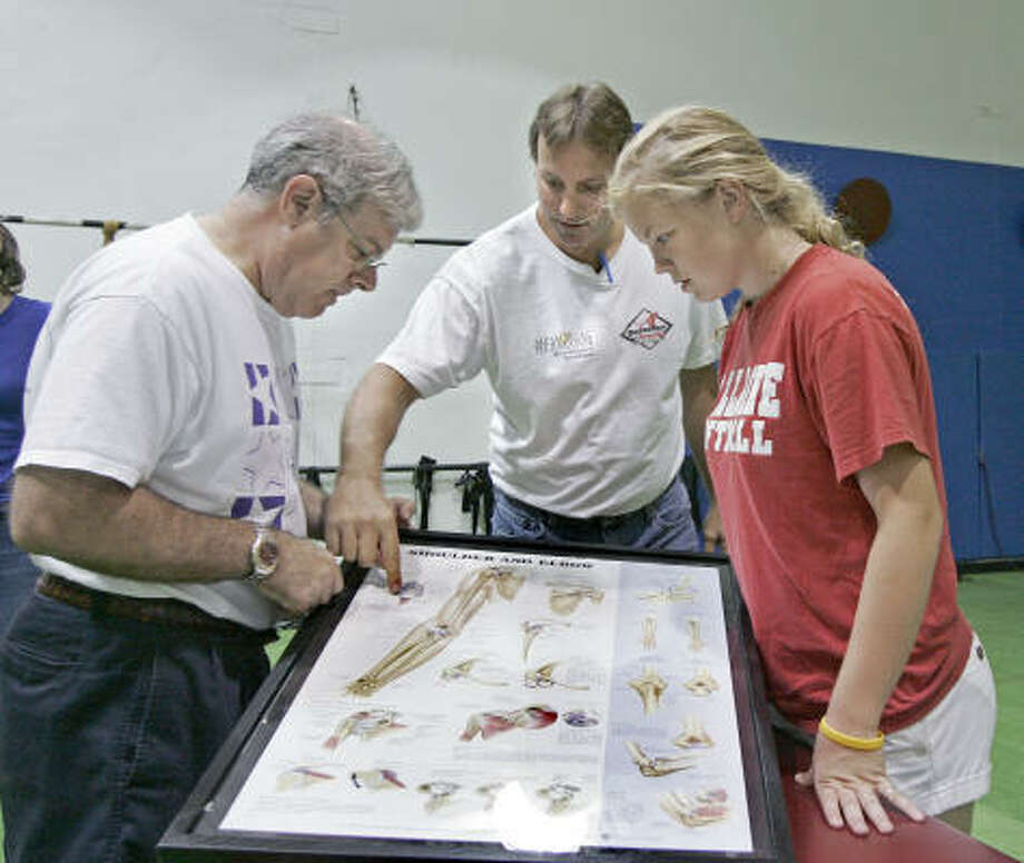 Dr. Charles Metzger, center, describes how he released an overly tight ligament in 16-year-old Brooke Forgetta's shoulder, right, to her uncle Stephen Ullrich. Photo: Craig Hartley, For The Chronicle