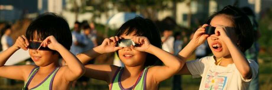 Children watch the solar eclipse Friday in Haikou, on southern China's Hainan island. Photo: STR, GETTY IMAGES