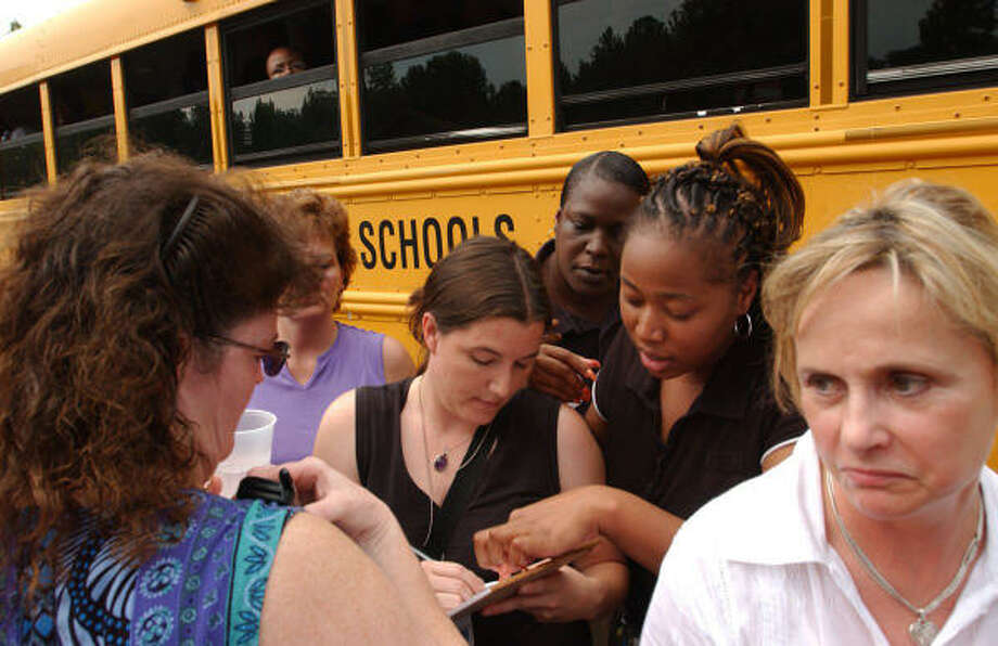 Parents gather around Orange School System employee Beth Creech, center, who was taking down the names of teenagers who had not shown up yet at a nearby church. Photo: HARRY LYNCH, AP