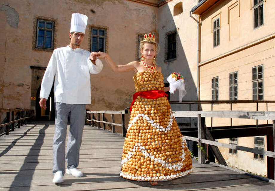 Valentyn Shtefano and his bride, Viktoriya, show off the wedding gown he baked for their August ceremony. Photo: AP