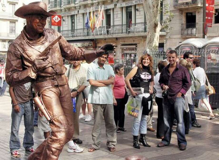 Luis Alberto Sila Almeda, posing as a cowboy, is one of the most popular living statues on Las Ramblas boulevard in Barcelona, Spain. By noon each day, the street is transformed into an outdoor theater crowded with tourists and passers-by. Photo: John Ward Anderson, Washington Post