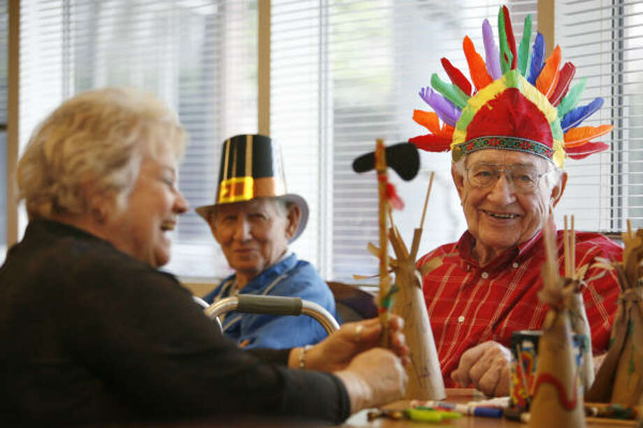 Family support activity coordinator Joan Arnold helps Walter Williams, right, during arts and crafts time at the Sheltering Arms Adult Day Center. Photo: Mayra Beltran, Chronicle