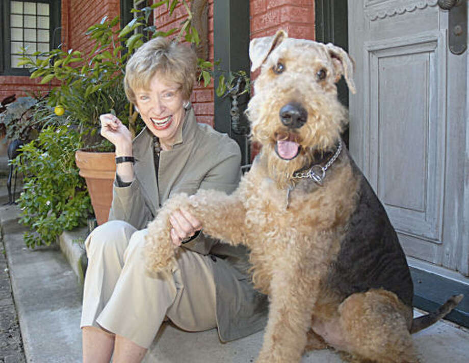 Gayle Ramsey and her dog, Clancy, sit in the courtyard of her 1928-era home in the Montrose area. Photo: TIM JOHNSON, CHRONICLE-NEIGHBORHOOD NEWS