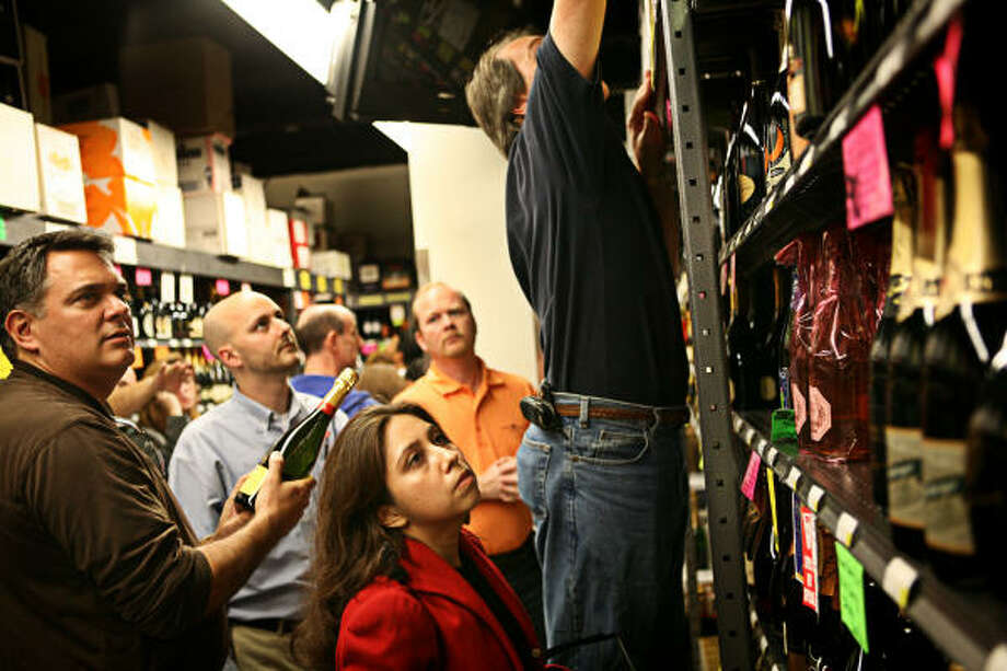 Garry Olah, left, and Cristela Henriquez, center, try to decide which champagne to buy for New Year's Eve at Spec's Spirits Wine & Finer Foods in Midtown Houston on Saturday. Photo: ERIN TRIEB, FOR THE CHRONICLE