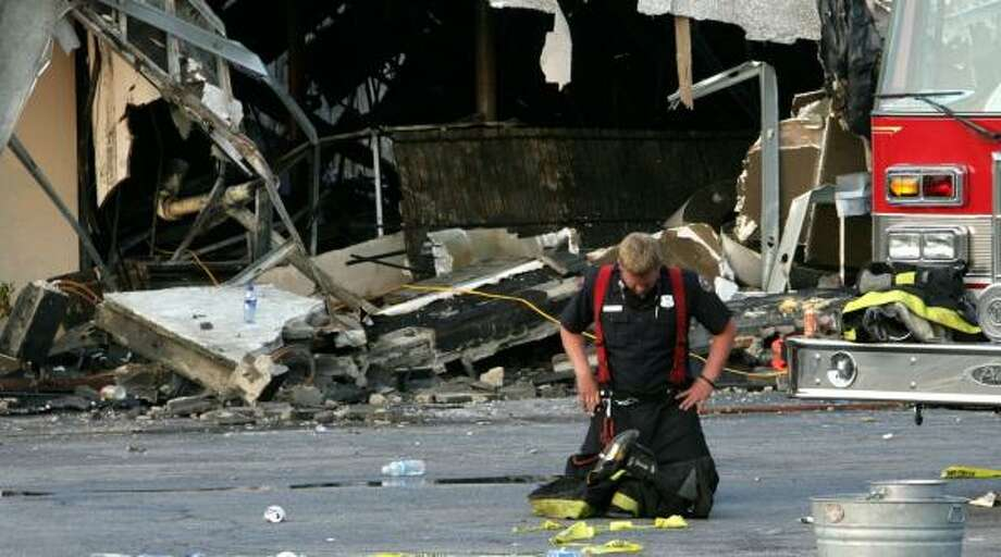 A firefighter takes a moment Tuesday morning after helping to put out the fire that claimed the lives of nine colleagues in Charleston, S.C. The fire broke out Monday night. Photo: ALICE KEENEY, Ap