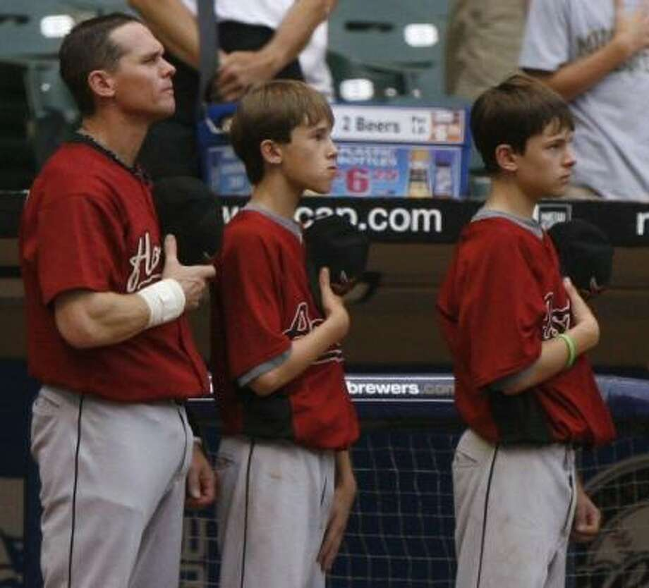 Craig Biggio stands during the national anthem with sons Cavan, 12, and Conor, 14. Photo: KAREN WARREN, CHRONICLE