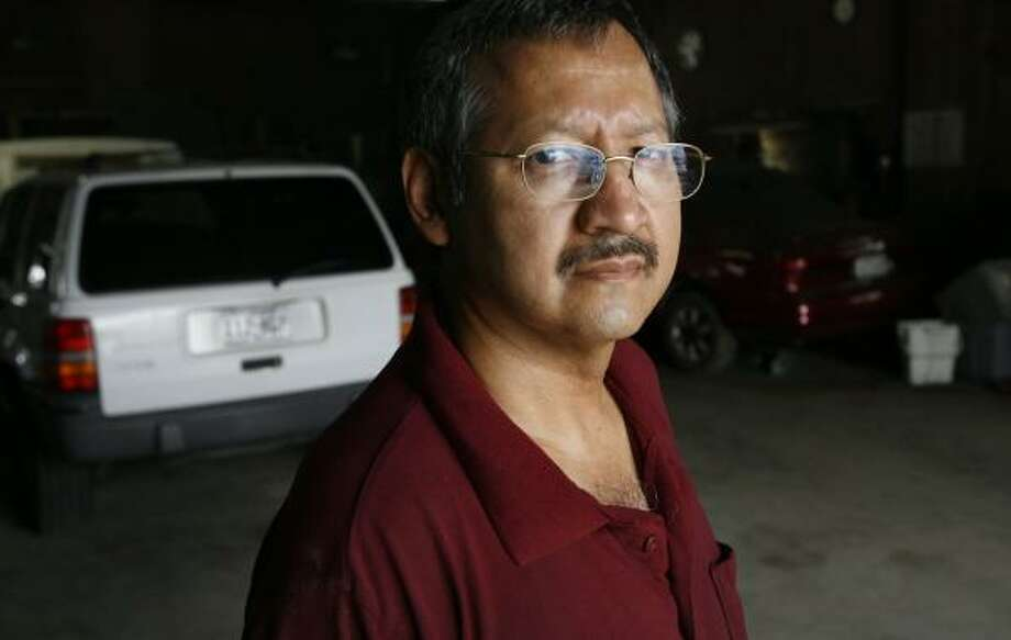 Arnie Serrano of A&J Auto Repair said the $3,000 voucher is not enough to buy another car in exchange for a problematic vehicle an owner now drives. The two vehicles in the background are his old cars. Photo: Kevin Fujii, Chronicle