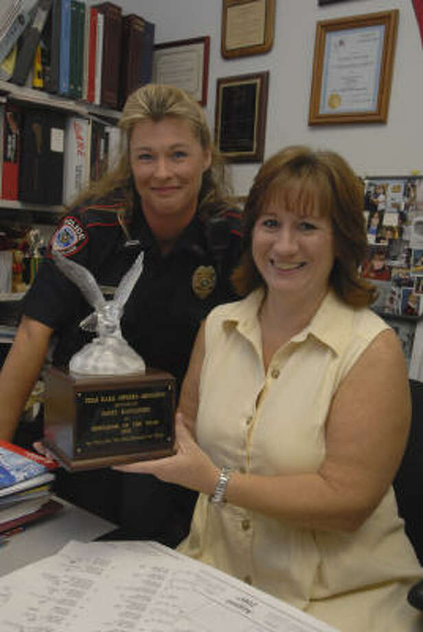 Jersey Village Police Officer Sandy Joachim stands next to Janet Rancatore as she holds the trophy presented to her for being named Educator of the Year for 2007 by the Texas DARE Officer's Association. Photo: Tony Bullard, FOR THE CHRONICLE