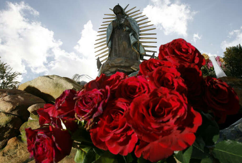 Stacks of flowers adorn a statue of the Virgin of Guadalupe at Our Lady of Guadalupe Church on Navigation. Every year, on the eve of her Dec. 12 feast day, about 20,000 pilgrims descend on the church to drop off flowers and view the statue. Photo: Sharon Steinmann, Chronicle