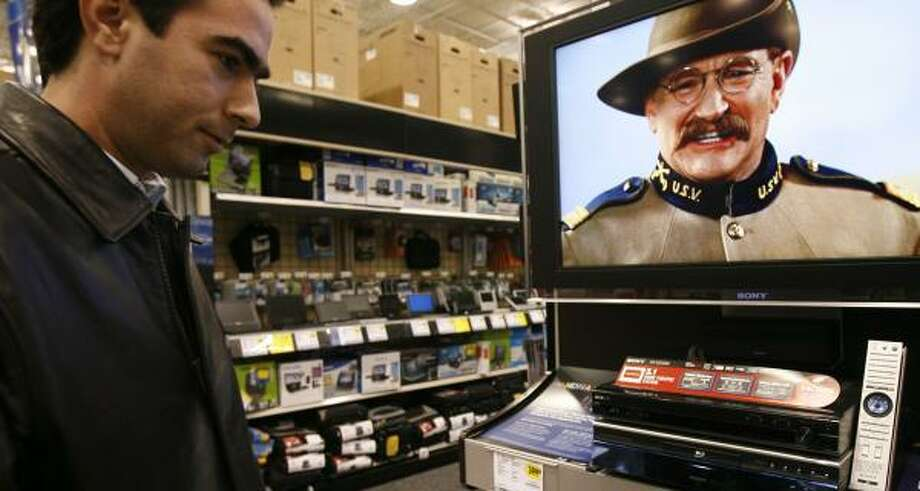 Raul Maldonado of Monterrey, Mexico, checks out Blu-ray Disc players at Best Buy on Richmond. Blu-ray and HD DVD are vying to be the future of home video, but many film fans are waiting to choose. Photo: JAMES NIELSEN, CHRONICLE